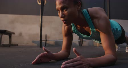 hajló : Front view close up of an athletic mixed race woman wearing sports clothes cross training at a gym, working out in the plank position, slow motion