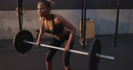 cross training : Front view of an athletic mixed race woman wearing sports clothes cross training at a gym, leaning forward and lifting weights on a barbell, slow motion