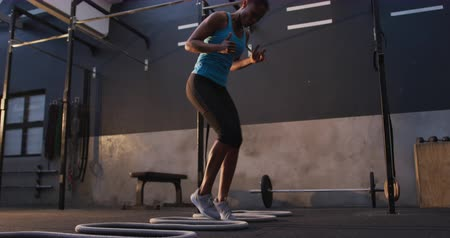 cross training : Low angle side view of an athletic mixed race woman wearing sports clothes cross training at a gym stepping sideways over tubes, slow motion Stock Footage