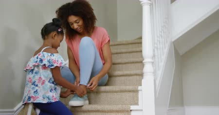 реальный : Front view of an african american mother sitting on the stairs in the hallway at home, and her young daughter kneeling in front of her helping her tying shoelaces for her mother, slow motion