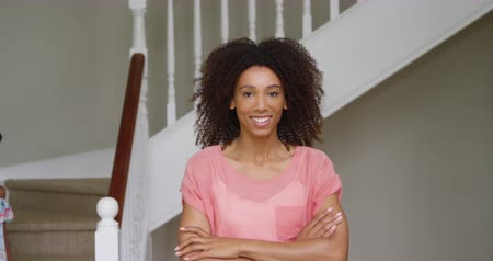 crossed : Portrait of an african american mother standing in the hallway at home with arms crossed, smiling to camera, with her young daughter walking down the stairs and passing behind her, slow motion
