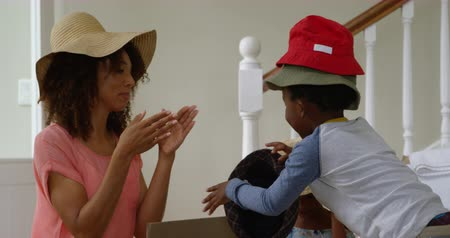headwear : Side view close up of an african american mother having fun in the hallway of her new home with her young son and daughter, trying on hats as they unpack a box, slow motion