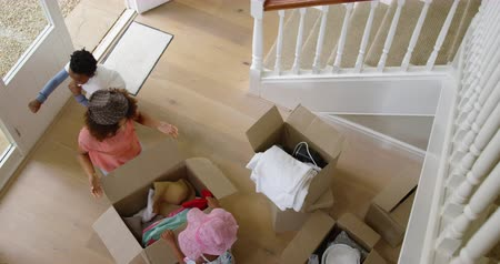 ajoelhado : High angle view of an african american mother in the hallway of her new home kneeling and unpacking a box of hats with her young son and daughter helping and playing, slow motion