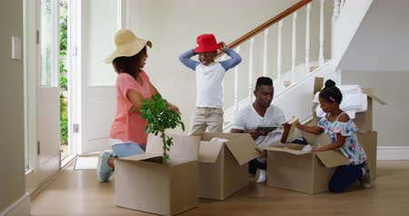 headwear : Front view of an african american family and their young son and daughter unpacking boxes together in the hallway of their new home, the mother and son trying on hats, slow motion