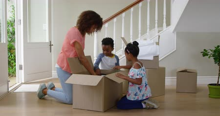 ajoelhado : Side view of an african american mother  in the hallway of her new home kneeling and unpacking a box of hats with her young son and daughter, slow motion