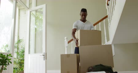 выполнять : Front view of an African American man carrying a carboard box through the front door and stacking it on a pile of boxes in the hallway of his new home, resting for a moment and smiling, slow motion