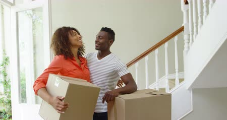выполнять : Front view of an African American couple standing beside a pile of boxes in the hallway of their new home, the woman carrying one, resting for a moment, looking around and smiling, slow motion Стоковые видеозаписи