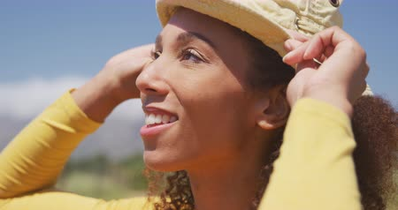 sunhat : Side view close up of a happy African American woman standing in a sunny field wearing a hat, holding the brim and smiling, slow motion