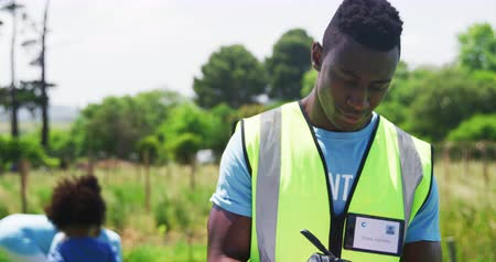panoya : Portrait close up of a young African American man standing in a field wearing a hi-vis vest and gloves, writing on a clipboard, looking up and smiling to camera, while volunteers collect rubbish and recycling in the background, slow motion