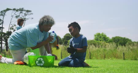 ajoelhado : Side view of a senior African American woman and young boy kneeling in a field wearing gloves and t shirts with volunteer written on them, filling a green plastic recycling crate and talking, with a diverse group of volunteers collecting rubbish and recyc Vídeos