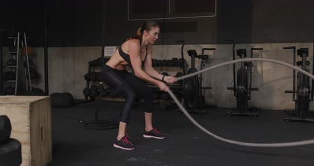 cross training : Side view of an athletic Caucasian woman wearing sports clothes cross training at a gym using battle rope. Health and Fitness concept.