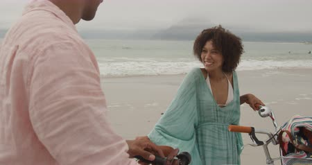 roupa de praia : Side view of an African American couple on a beach by the sea, holding bicycles and talking, slow motion. Romantic Vacation Concept. Vídeos