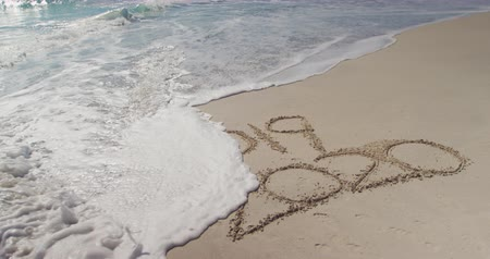 bin : 2019 and 2020 written in the sand on a sunny beach with calm sea washing away the years, slow motion