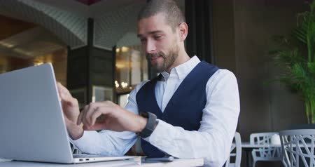 kısa : Front view of a young smiling Caucasian businessman in a cafe, checking time on his smartwatch while working on laptop computer, slow motion