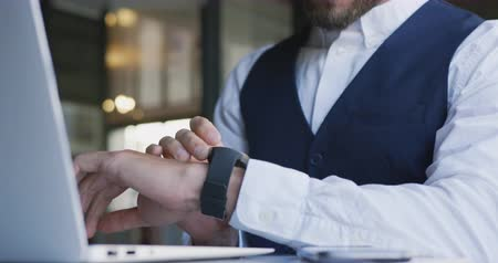 employed : Front view of a young smiling Caucasian businessman in a cafe, checking time on his smartwatch while working on laptop computer, slow motion