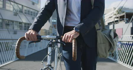 ciclismo : Front view mid section of a young Caucasian businessman on the go in the city, walking with a bike in the street with buildings in the background, slow motion Stock Footage