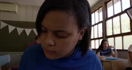 spolužák : Front view close up of a stressed teenage mixed race schoolgirl sitting at a desk in class using a tablet computer and looking confused, with classmates working in the background, slow motion