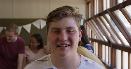 recess : Portrait close up of a Caucasian teenage boy with short hair and grey eyes standing in a school classroom smiling to camera, with classmates talking in the background, slow motion