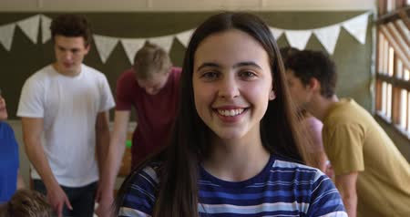 recess : Portrait close up of a teenage Caucasian girl with long, dark hair and brown eyes standing in a school classroom smiling to camera, with classmates talking in the background