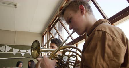 rehearsing : Side view close up of two Caucasian teenage male musicians rehearsing, one playing the French horn and one playing the trombone, with other teenage musicians in the background, slow motion