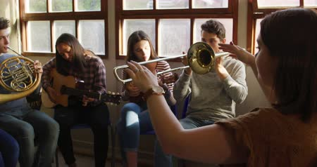 high school : Side view of a Caucasian woman sitting and conducting a multi-ethnic group of male and female teenage musicians playing at a school band practice, slow motion Stock Footage