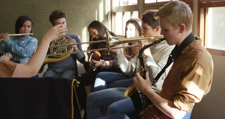 high school : Side view of a multi-ethnic group of male and female teenage musicians playing at a school band practice, with the arm of a Caucasian female conductor in the foreground, slow motion