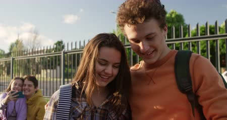 schoolyard : Front view of a Caucasian teenage girl and boy embracing and smiling while the boy takes a selfie of them with a smartphone in their school grounds, another teenage couple sitting in the background, slow motion Stock Footage