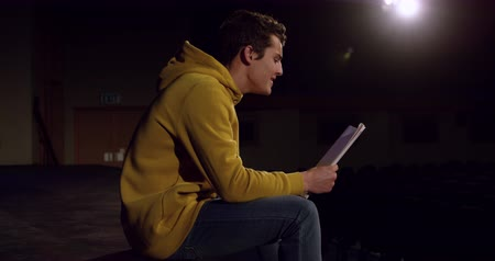 vokal : Side view of a teenage Caucasian boy sitting on the the stage in an empty school theatre reading from a script during rehearsals for a performance, slow motion