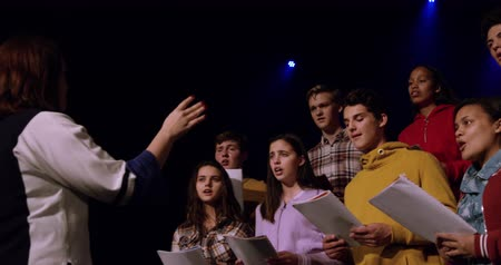 dyrygent : Side view of a Caucasian female conductor directing a multi-ethnic group of teenage male and female choristers holding sheet music and singing, standing on the stage of a school theatre during rehearsals for a performance, slow motion