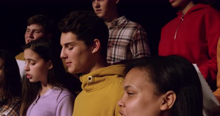 coro : Side view close up of a multi-ethnic group of teenage male and female choristers holding sheet music and singing, standing on the stage of a school theatre during rehearsals for a performance, slow motion