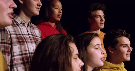 rehearsing : Side view close up of a multi-ethnic group of teenage male and female choristers singing, standing on the stage of a school theatre during rehearsals for a performance, slow motion