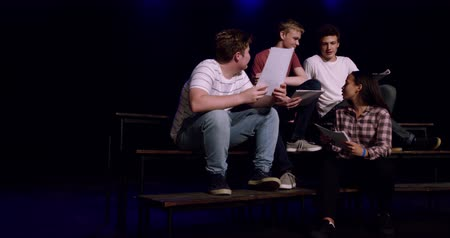 rehearsing : Front view of three teenage Caucasian boys and a teenage mixed race girl holding scripts, talking and smiling, sitting on the stage of a school theatre during rehearsals for a performance, slow motion Stock Footage