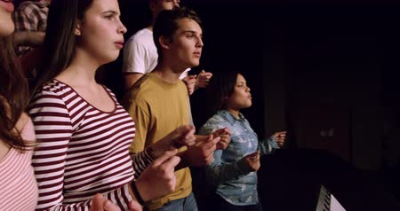 rehearsing : Side view close up of a multi-ethnic group of teenage male and female choristers and a Caucasian female conductor, clicking their fingers and singing, standing on the stage of a school theatre during rehearsals for a performance, slow motion Stock Footage