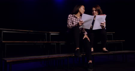 rehearsing : Front view of a teenage Caucasian and a teenage mixed race girl holding scripts and talking to each other, sitting on the stage of a school theatre during rehearsals for a performance, slow motion