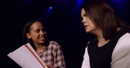 acteren : Side view close up of a teenage Caucasian and a teenage mixed race girl holding scripts and talking to each other, sitting on the stage of a school theatre during rehearsals for a performance, slow motion
