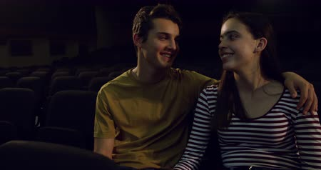 rehearsing : Front view of a teenage Caucasian girl and boy sitting together in the empty dark auditorium of a school theatre, the boy with his arm around the girl, both watching a performance, turning to smile at each other and touching heads, slow motion Stock Footage