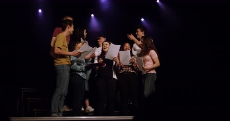 high school : Front view of a multi-ethnic group of teenage male and female choristers holding scripts, talking and smiling, standing on the stage of a school theatre during rehearsals for a performance