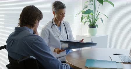 recovering : In the hospital, Side view of a Caucasian female doctor holding up an x ray and showing it to a Caucasian male patient in a wheelchair and talking, during a consultation in an office at a hospital 4k Stock Footage