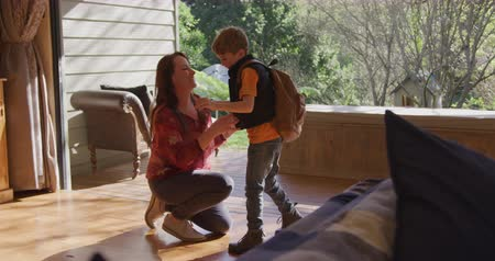 a genoux : Side view of a caucasian mother at home in the living room, kneeling and hugging her young son who is standing and wearing a rucksack, slow motion 4k Vidéos Libres De Droits
