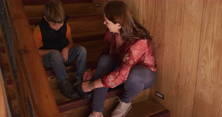 tying : High angle view of a caucasian mother and her young son at home, sitting on the stairs talking, while the mother ties his shoelaces, slow motion 4k