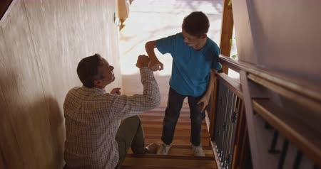 çarpmak : High angle view of a Caucasian man and his young son at home, the father sitting on the stairs and the son standing, they high five, fist bump and embrace, slow motion 4k