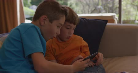 sharing : Side view close up of two young Caucasian brothers at home in the living room, sitting on a sofa and using a tablet computer together and smiling, slow motion 4k