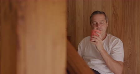 schody : Front view of a Caucasian man at home, sitting on the stairs leaning against the wall, drinking a cup of coffee and thinking, slow motion