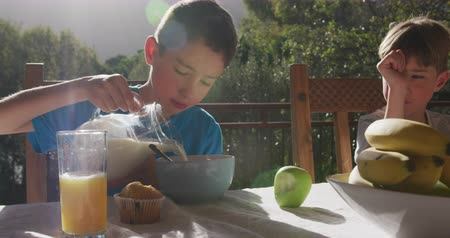 korsó : Front view of two Caucasian brothers at home, sitting outside on a terrace at a table in the sun for breakfast, the older brother pouring milk from a jug into a bowl of cereal, slow motion Stock mozgókép