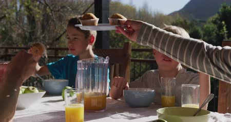 korsó : Side view of a Caucasian couple and their two sons at home, sitting outside on a terrace at a table for breakfast in the sun, the mother offering a plate of muffins around the table, slow motion