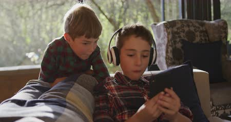 reclináveis : Front view close up of two young Caucasian brothers at home in the living room, the older brother sitting on the sofa wearing headphones and using a smartphone, the younger brother standing behind and looking over his shoulder, slow motion Vídeos