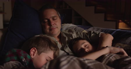 reclináveis : Front view close up of a Caucasian man and his two young sons at home in the living room, lying on the sofa asleep, the father in the middle with both sons leaning on his chest, his arm around his younger son, slow motion Vídeos