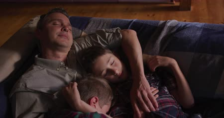 reclináveis : Front view close up of a Caucasian man and his two young sons at home in the living room, lying on the sofa asleep, the father with his arm around his older son, the son leaning on his father with his arm around his younger brother, slow motion Vídeos