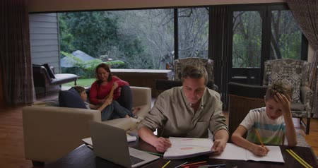 writings : High angle view of a Caucasian man and his young son at home in the living room, sitting at a table talking, the father helping his son with homework, open schoolbooks and a laptop computer on the table in front of them, with the mother and brother sittin Stock Footage