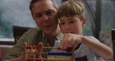 abacus : Front view close up of a Caucasian man and his young son at home in the living room, sitting at a table talking, the boy using an abacus on the table in front of them, slow motion